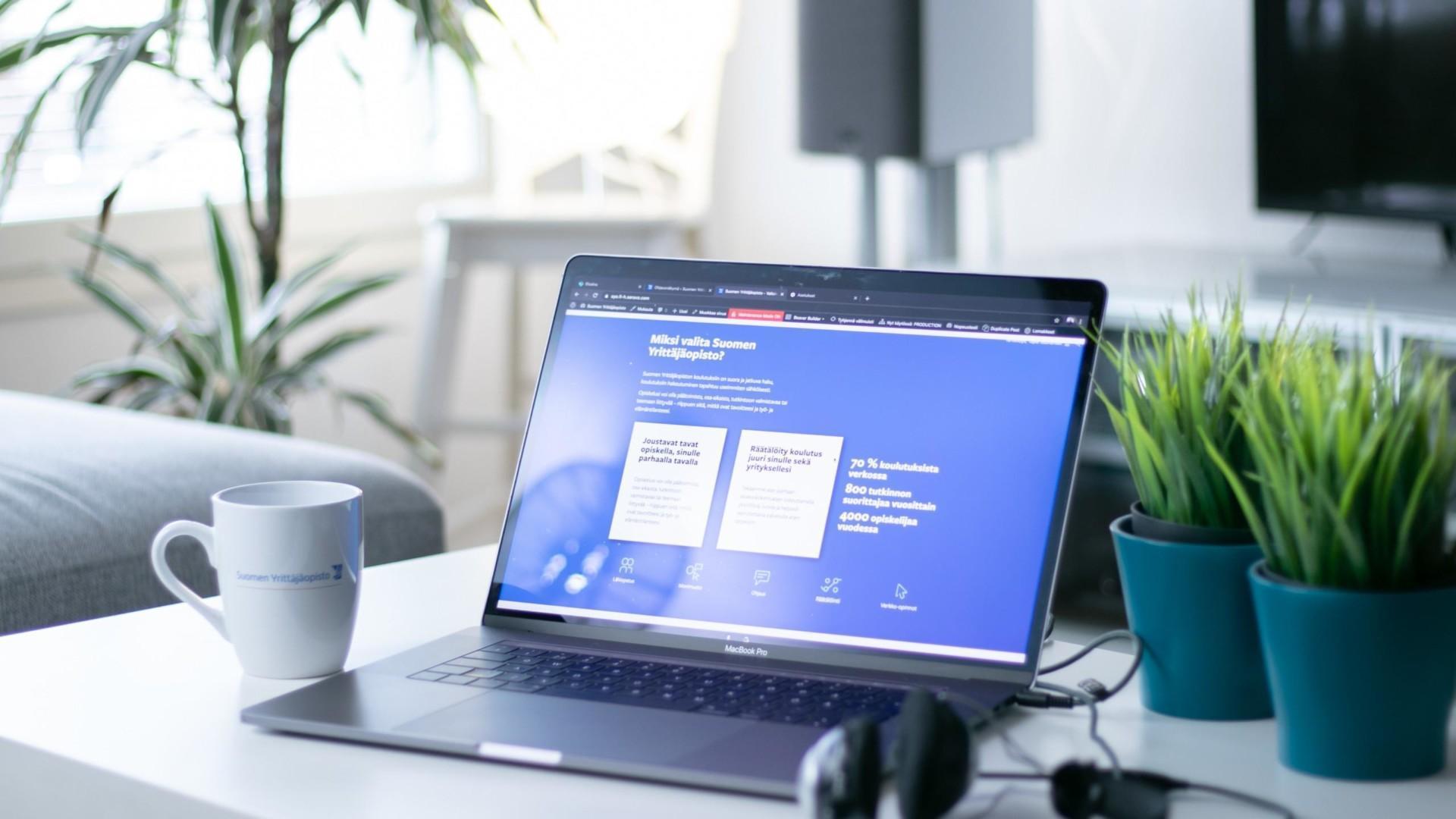 Tietokone ja kahvikuppi pöydällä.