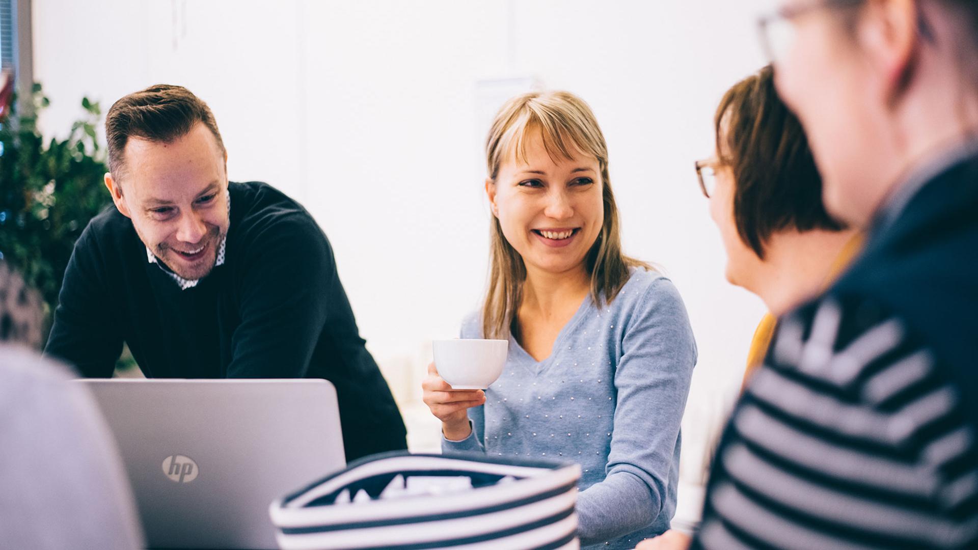 Neljä ihmistä keskustelee pöydän ympärillä kahvilla, pöydällä kannettava tietokone.