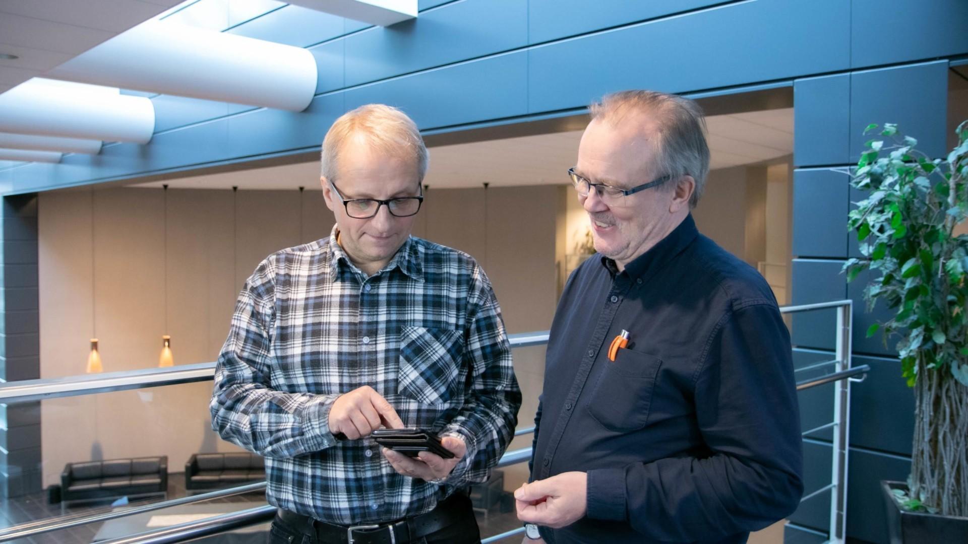 Työllistä taidolla, kaksi miestä tutkii puhelimesta palvelua.