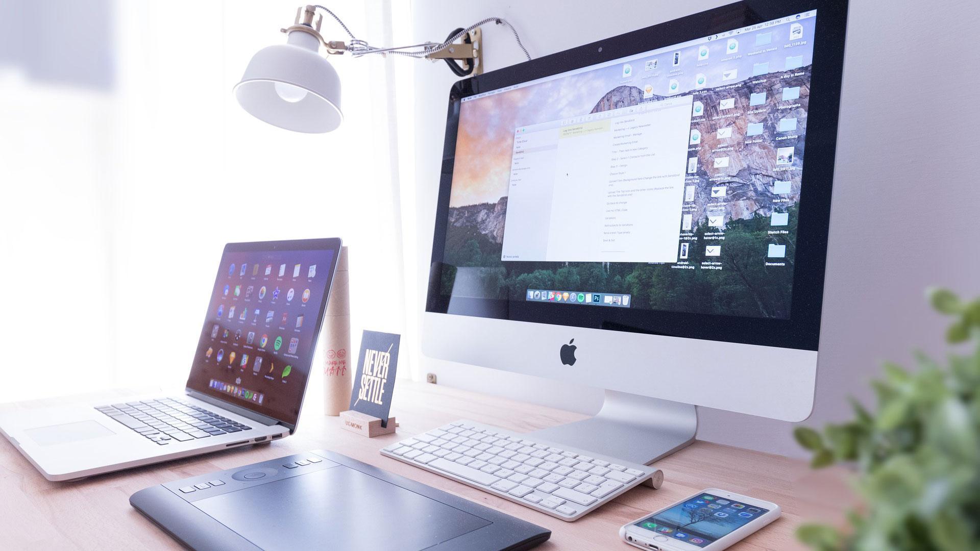 Pöydällä kannettava tietokone, pöytäkone ja matkapuhelin.