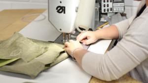 Ompelukoneella työskentelevä ompelija. Näkyvissä ompelijan kädet ja ommeltava tuote.