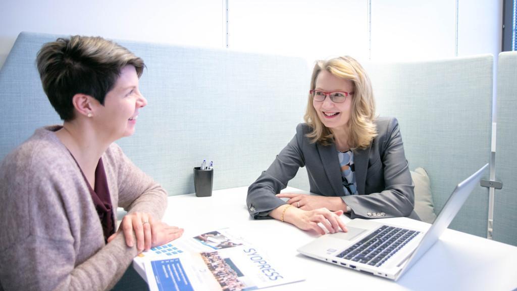 Kaksi naista pöydän ääressä keskustelemassa johtamisesta ja pöydällä heidän edessään kannettava tietokone.