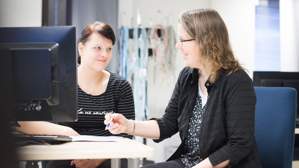 Johtajuuden tikkaat -hanke keskittyy maatalouden johtamiskulttuurin kehittämiseen. Kaksi naista keskustelee johtamisasioista pöydän ääressä tietokoneen ruudun edessä.