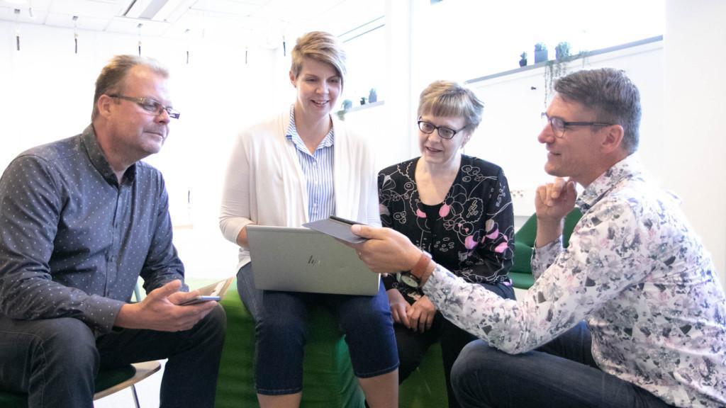 Kehittämispalvelut: neljä ihmistä kannettavan tietokoneen ympärillä.