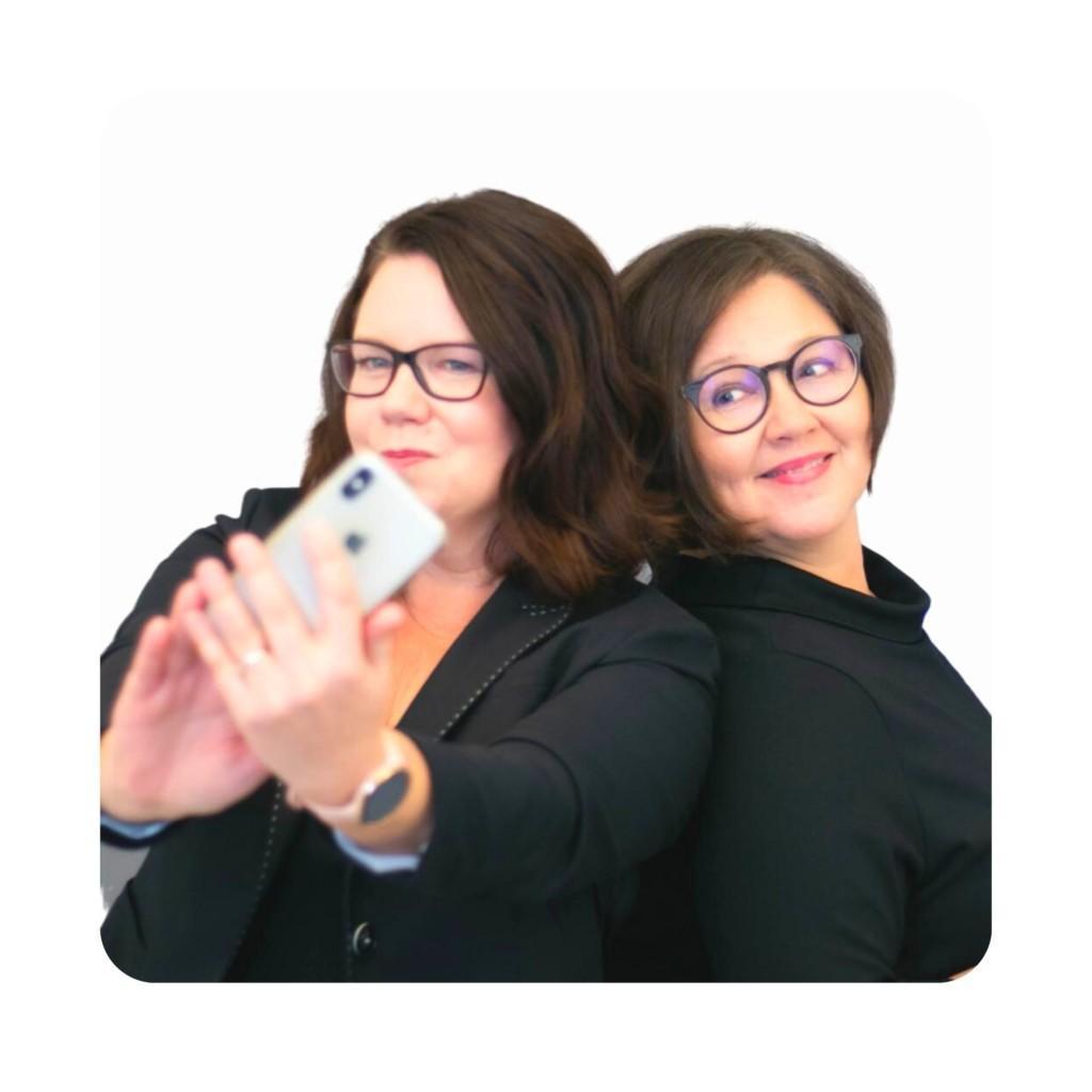 Kaksi naista poseeraa ja ottaa selfietä kännykällä.