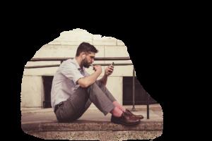 Nuori miesyrittäjä tutkii puhelinta ja kuuntelee kuulokkeilla,