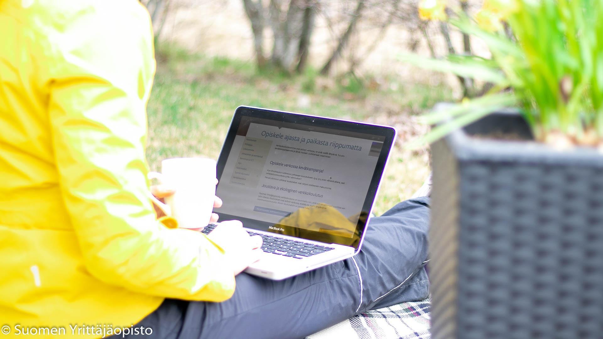 Nainen katsoo tietokonetta ulkona