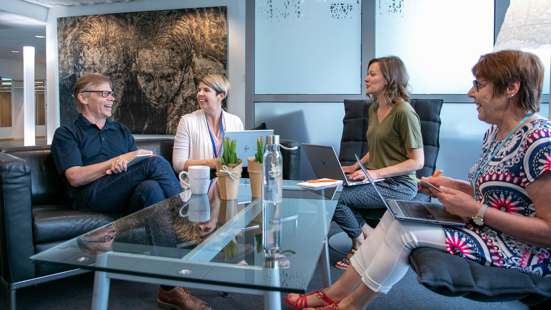 Kuntapäättäjät pöydän ääressä keskustelemassa ja opiskelemassa. Pöydällä kannettava tietokone.