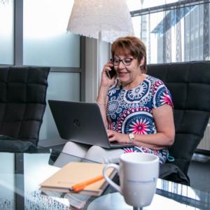Johtaja työskentelee työpöydän ääressä kannettavalla tietokoneella ja puhuu puhelimeen.