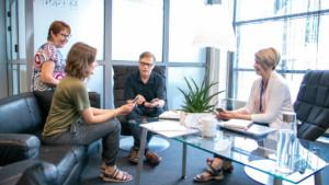 Kolme naista ja yksi mies keskustelevat pöydän ympärillä ja pitelevät kännyköitä.