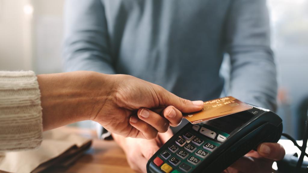 Asiakkaan käsi ojentuu maksupäätteelle. Kädessä pankkikortti. Taustalla seisoo myyjä.