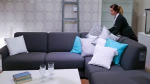 Nainen järjestelee sohvatyynyjä sohvalla.