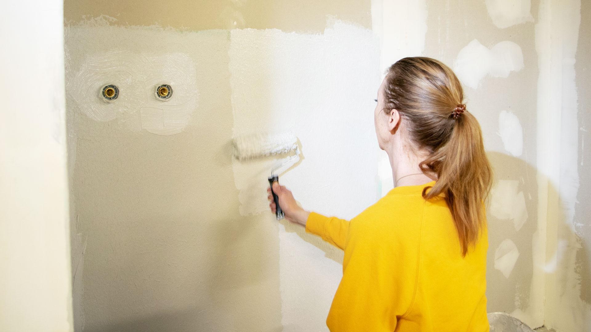 Nainen remontoi seinää, maalaa telalla seinää valkoiseksi.