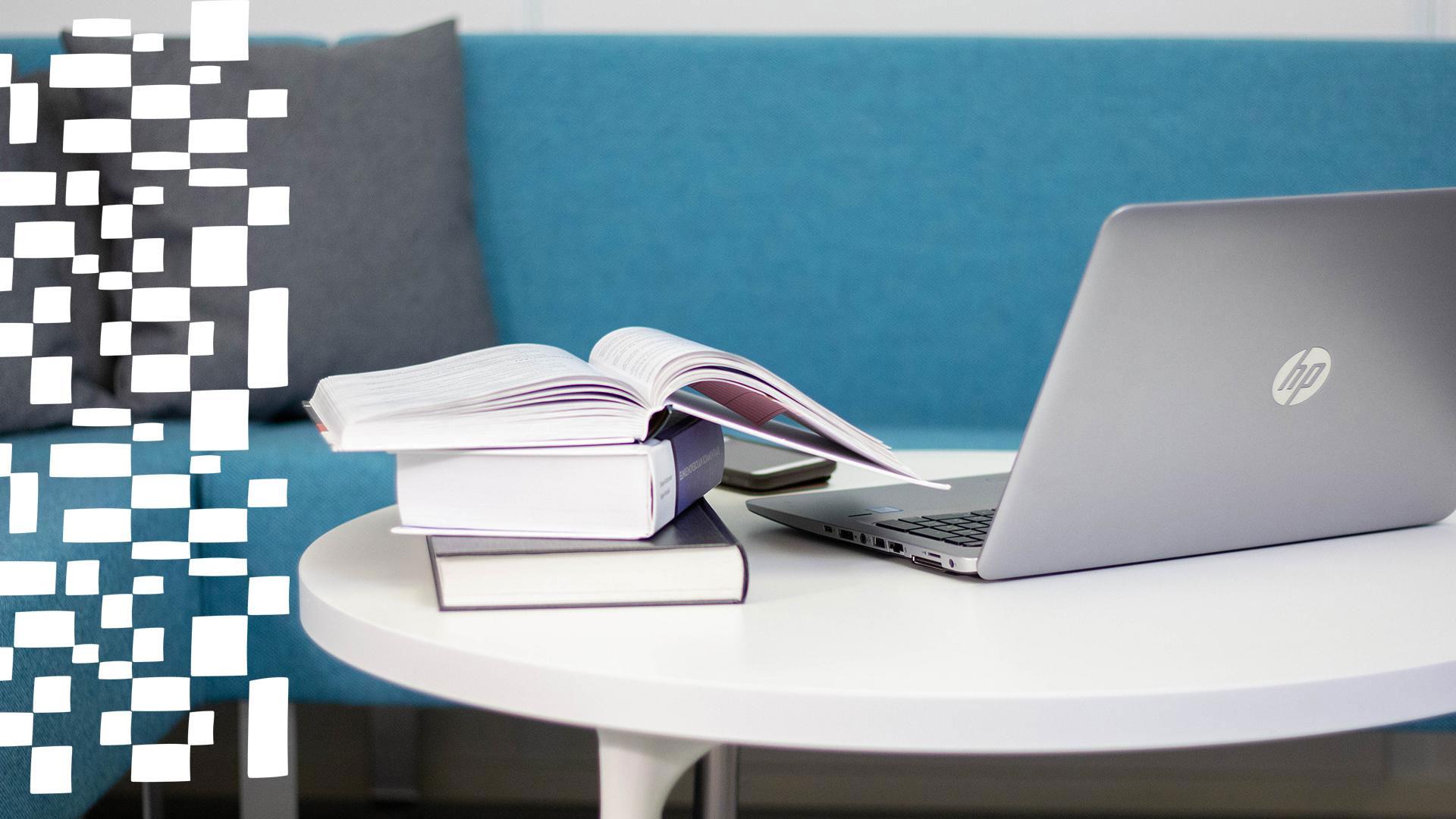 Tietokone ja kirjallisuutta pöydällä.